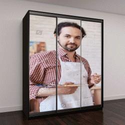 """Шкаф купе с фотопечатью """"Портрет талантливый профессиональный художник, работающий в арт-студии, позирует и улыбается в камеру рядом с его картин на мольберте"""""""